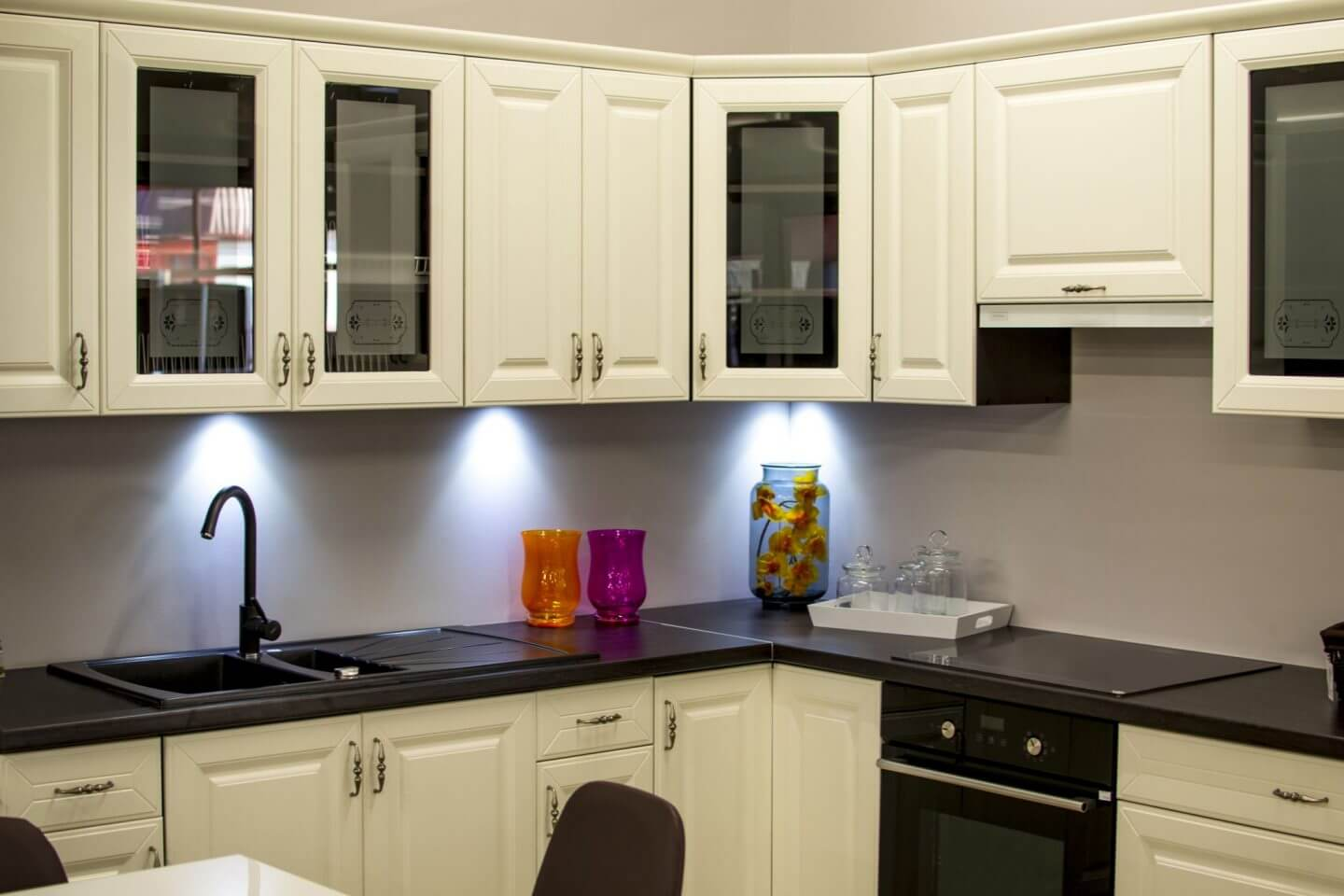 white kitchen with black worktops and downlights