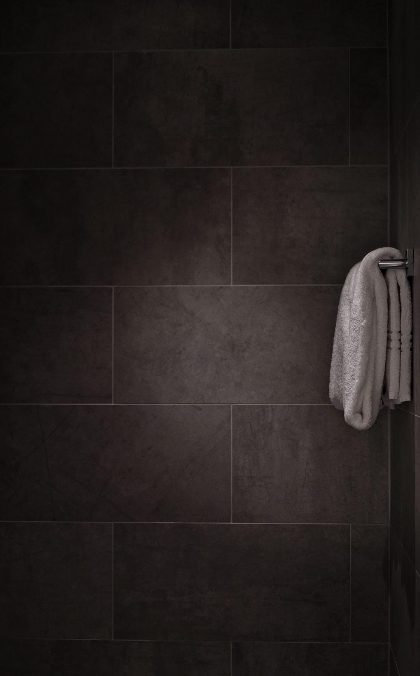 black bathroom tiles with white towel