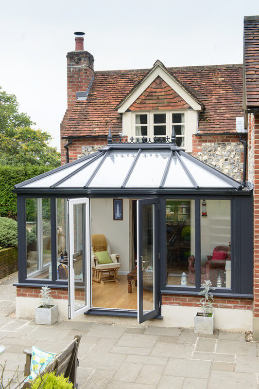 Large conservatory with glass and modern grey panels.