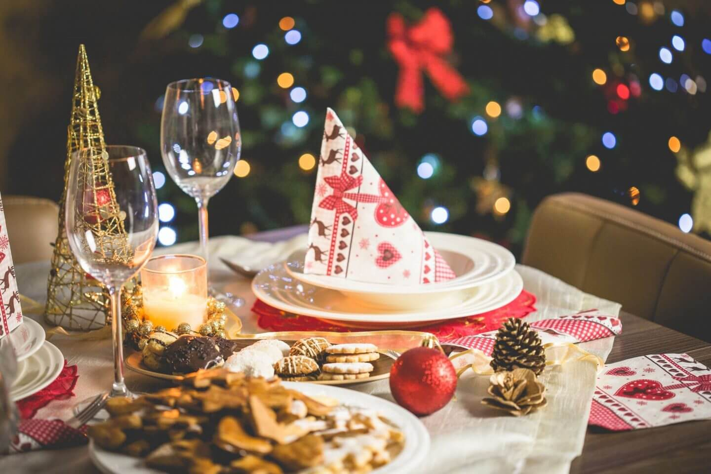 Red and gold themed table with white plates and Christmas napkins