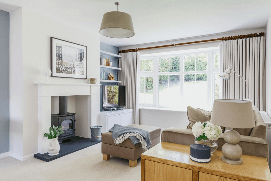 Home improvements include a log burner. White living room with black log burner and white fireplace surround