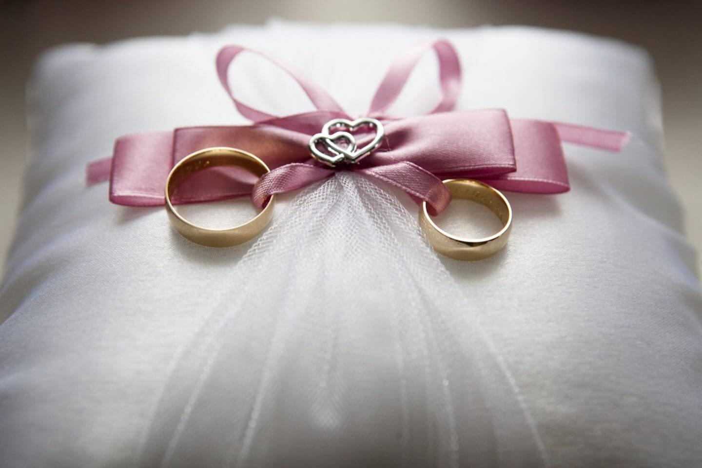 Wedding bands on a white pillow with pink ribbon
