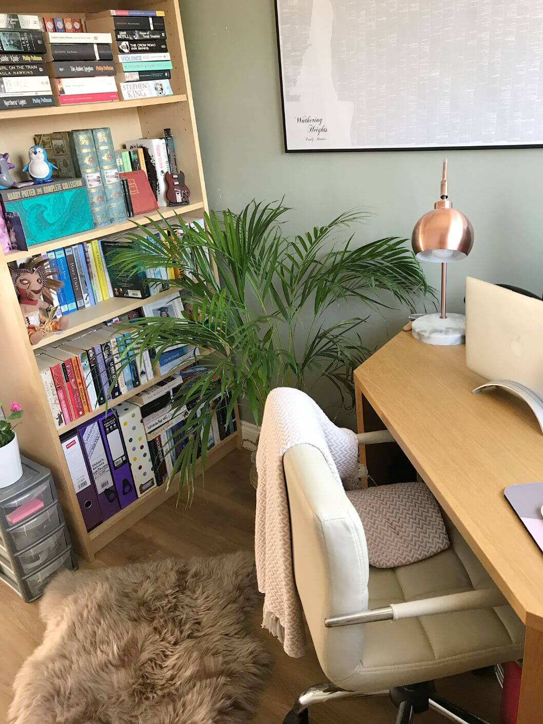Home office with large piece of art on the wall and colourful bookcase