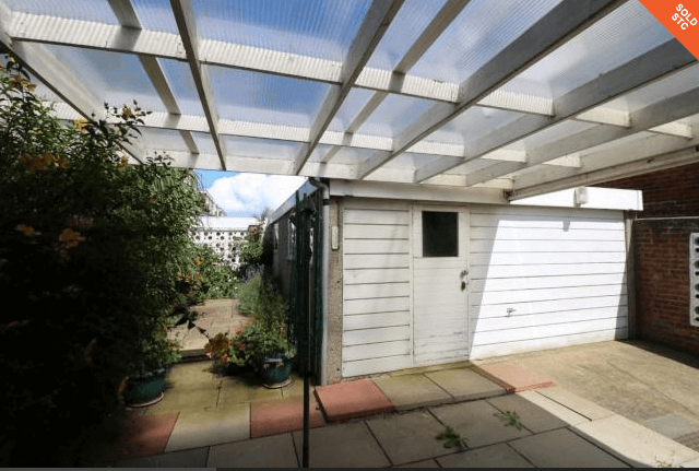Overgrown garden with garage - garden renovation plans are in place to transform it.