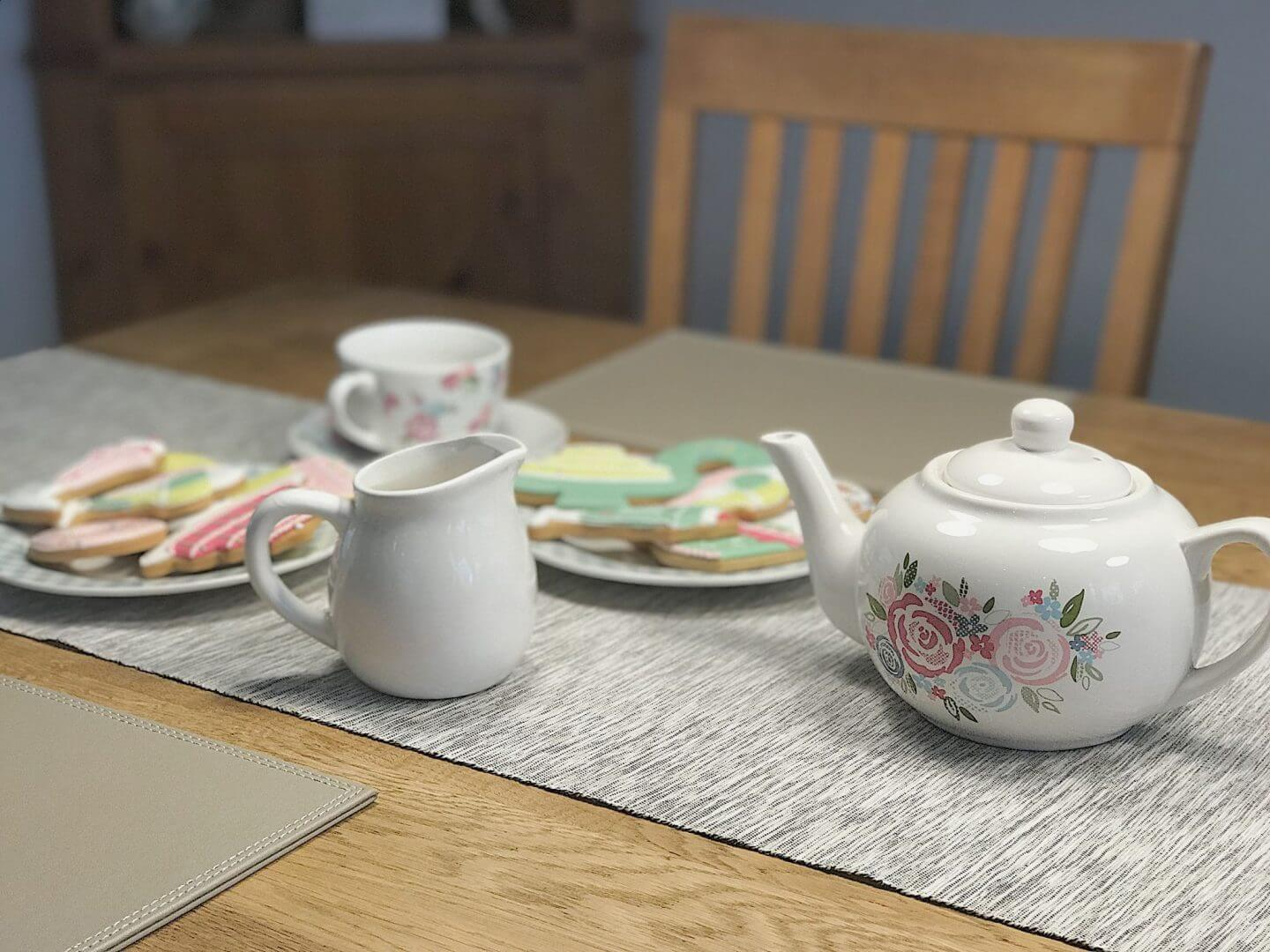 Tea set with yellow, pink and green iced biscuits on a plate
