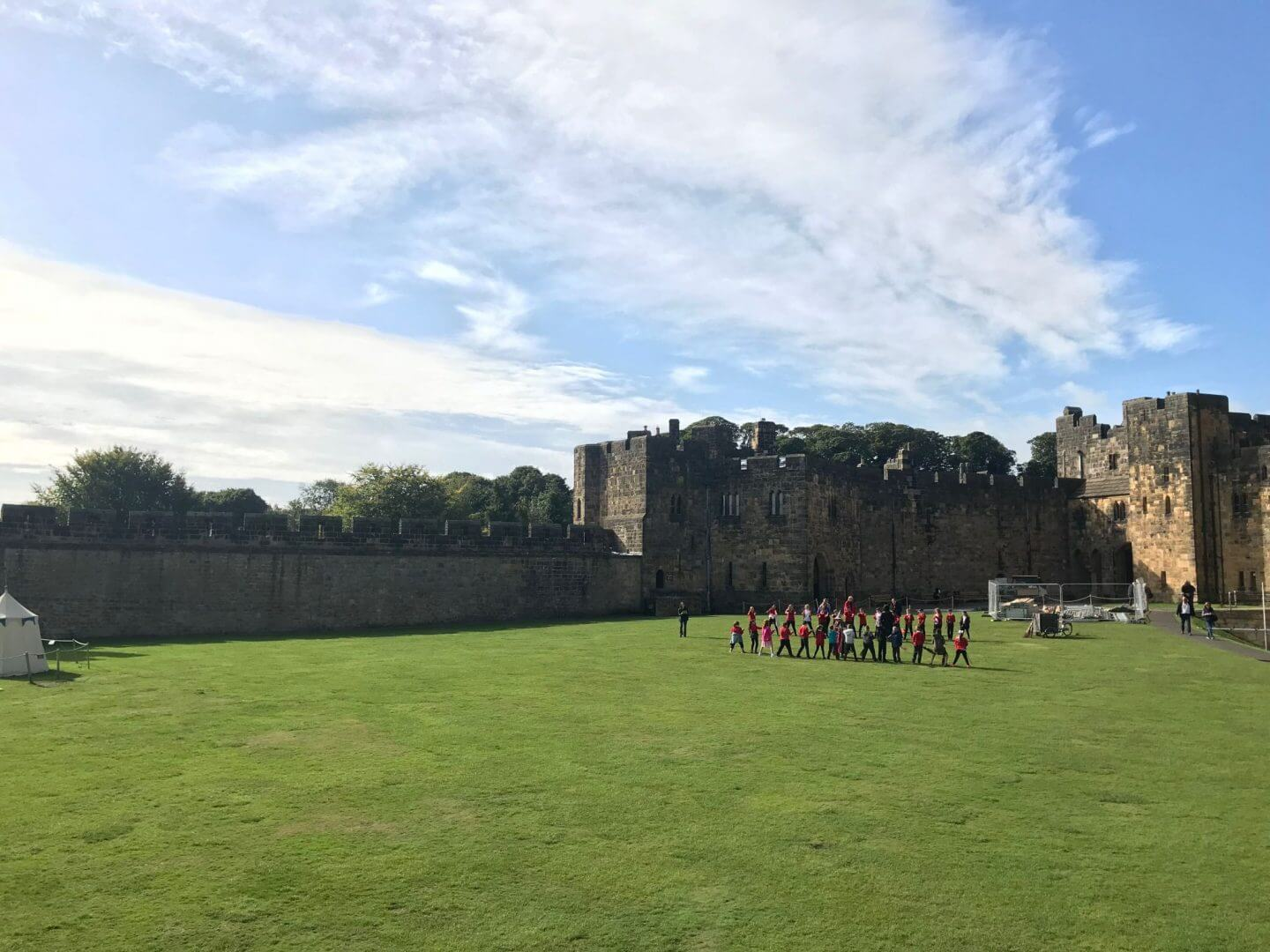 Alnwick castle in the sunshine with children and broomsticks