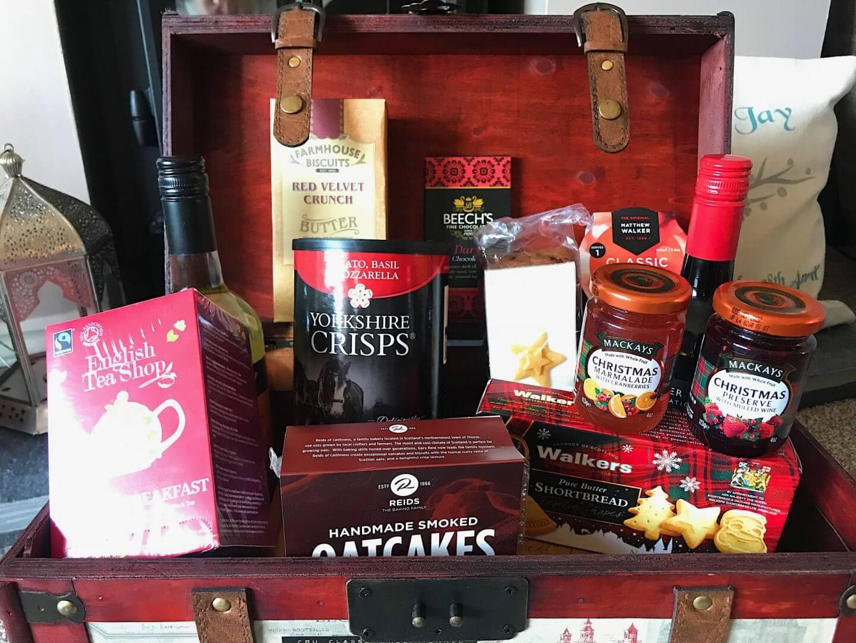 Close up of Prestige Christmas hamper showing wine, tea, biscuits, and crisps