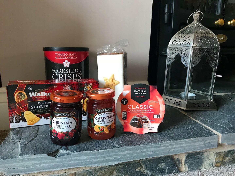Jams, crisps and Christmas pudding on slate hearth next to Christmas hamper