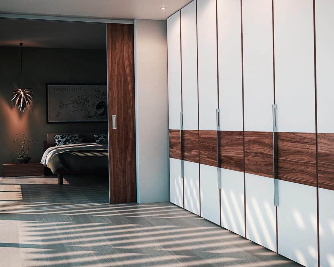 White and brown wardrobes with large sliding doors and a bed in the background