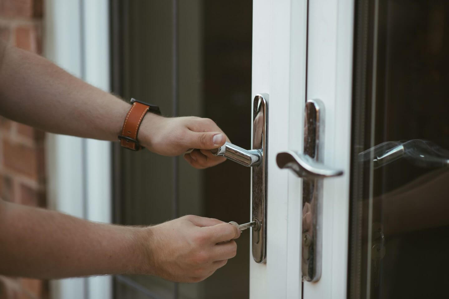 Protect your home when you're away: man locking back french doors with key