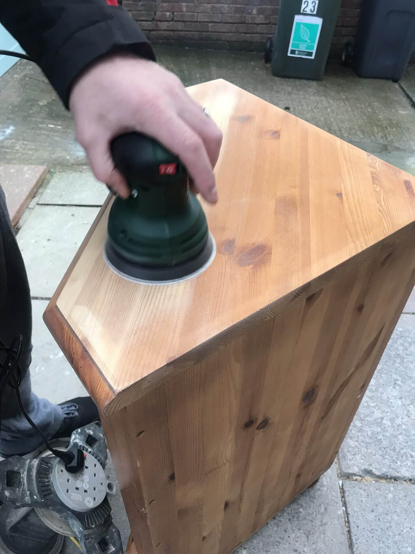 Jay using an orbit sander to sand down our cabinet