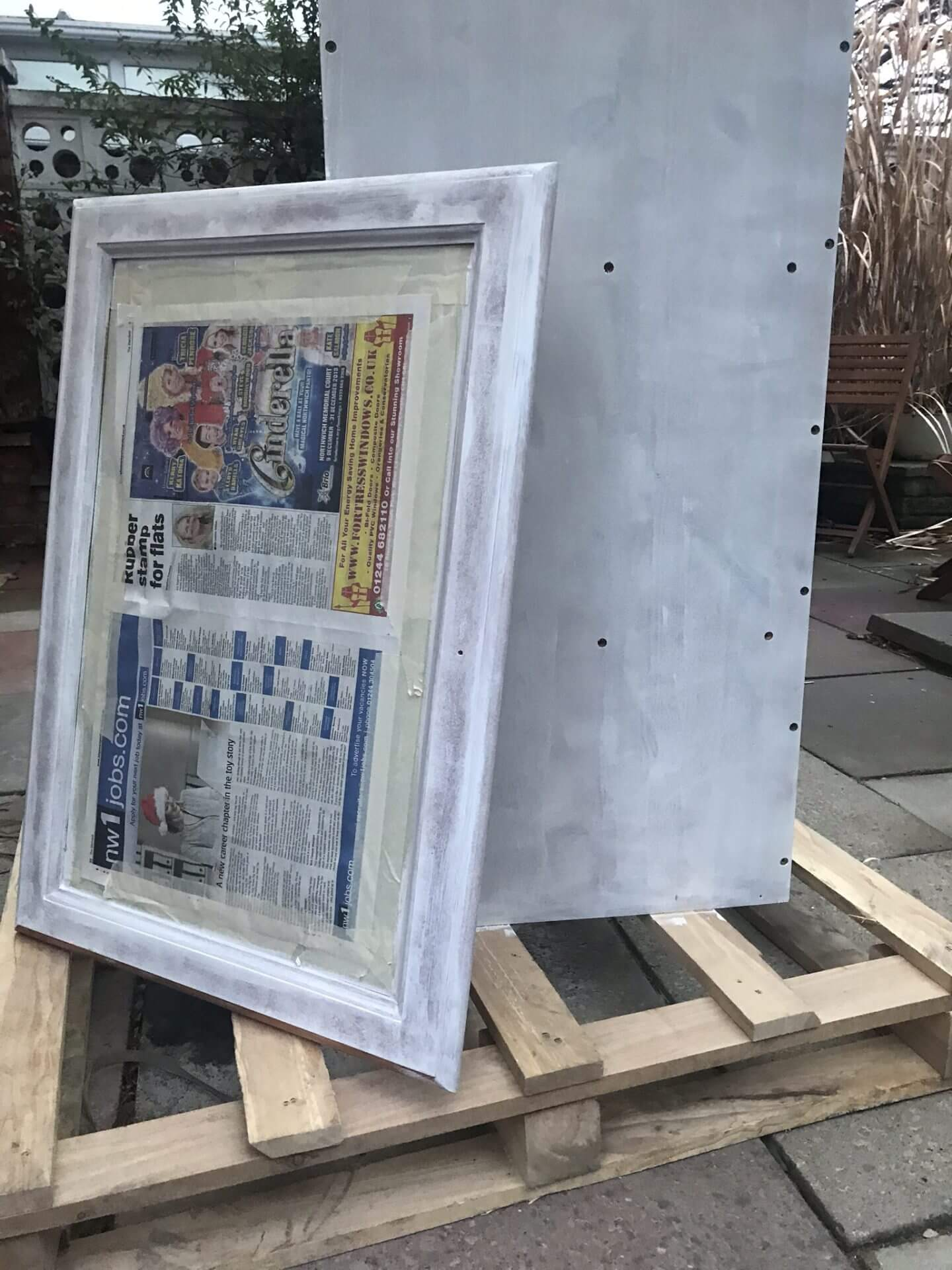 Glass door covered in newspaper leaning against the cabinet