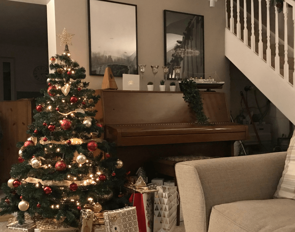 Living room with Christmas tree up showing how messy our under stairs is