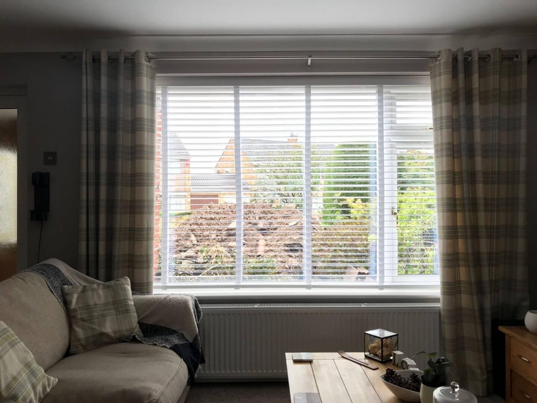 Wohnzimmer mit großem weißen Fensterladen wie Jalousien im Fenster mit Sofa und Couchtisch